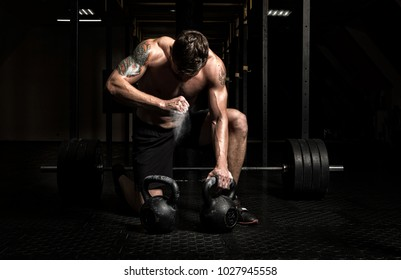 Muscular man workout with kettlebell at gym