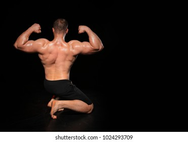 Muscular man's back in a dark background. muscular man
