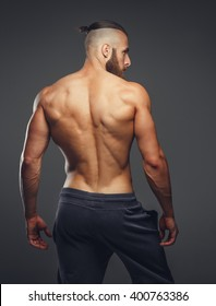 Muscular man's back on a grey background.