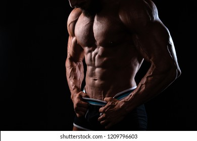 Muscular man's torso on black background with backlight