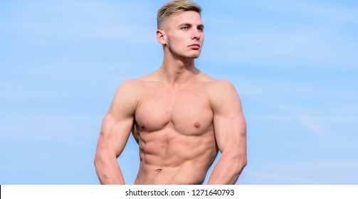 Muscular masculine guy look confident. Man muscular torso stand confidently. Sportsman muscular torso posing. Sport and bodycare. Man sexy muscular bare torso stand outdoor blue sky background.