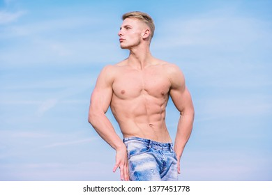 Muscular masculine guy look confident. Man sexy muscular bare torso stand outdoor blue sky background. Man muscular torso stand confidently. Sportsman muscular torso posing. Sport and bodycare.