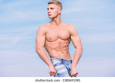 Muscular masculine guy look confident. Man muscular torso stand confidently. Sport and bodycare. Man sexy muscular bare torso stand outdoor blue sky background. Sportsman muscular torso posing.