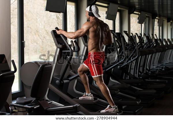 Muscular Mature Man Doing Aerobics Elliptical Walker In Modern Fitness Center