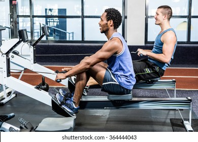 Muscular men using rowing machine at gym