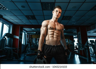 Muscular model sports young man exercising in gym. Portrait of sporty healthy strong muscle. Fitness trainer. Sport workout bodybuilding motivation concept. Sexy torso.