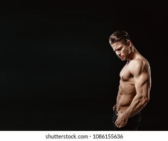 Muscular model sports young man on a dark background. Portrait of sporty healthy strong muscle guy. Sexy torso.