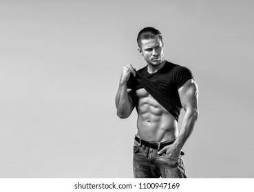 Muscular model sports young man in blue jeans raised his hand t-shirt and showing his press on a grey background. Black and white fashion portrait of sporty healthy strong muscle guy. Sexy torso.