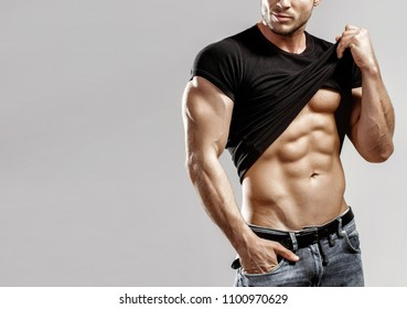 Muscular model sports young man in blue jeans raised his hand t-shirt and showing his press on a grey background. Fashion portrait of sporty healthy strong muscle guy. Sexy torso.