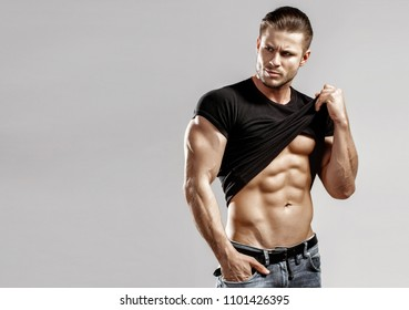 Muscular model sports young man in jeans and t-shirt showing his press on a grey background. Fashion portrait of sporty healthy strong muscle guy with a modern trendy hairstyle. Sexy torso.