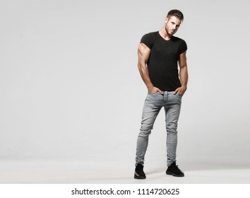 Muscular model sports young man in jeans and black t-shirt on a grey background. Fashion portrait of brutal sporty healthy strong muscle guy with a modern trendy hairstyle.