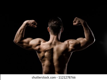 Muscular model sports young man on a dark background. Sporty healthy strong muscle guy showing his back and  big shoulders,biceps, triceps. Sexy male flexing his muscles. Workout bodybuilding concept.