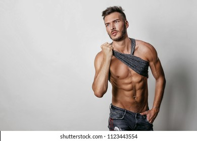 Muscular model sports young man in blue jeans raised his hand t-shirt and showing his press on a grey background. Fashion portrait of sporty healthy strong muscleguy. Sexy torso.