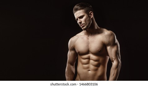 Muscular model sports young man on dark background. Fashion portrait of strong brutal guy with a modern trendy hairstyle. Sexy torso. Male flexing his muscles.