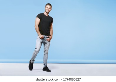 Muscular model sports young man in grey jeans and black t-shirt on blue background. Portrait of brutal muscle guy with modern trendy hairstyle. Fashion concept. Free space for text.