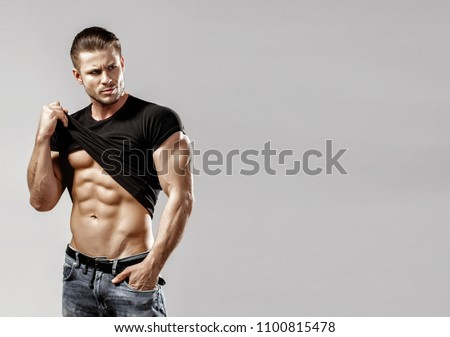 f6ec214d Muscular model sports young man in blue jeans raised his hand t-shirt and  showing