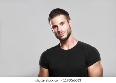 Muscular model young man with beard in black t-shirt on gray background. Fashion portrait of brutal sporty sexy strong muscle guy with modern trendy hairstyle. Model, fashion concept.