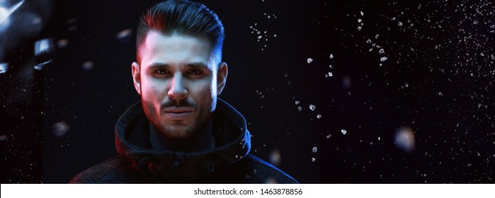 Muscular model young man with beard in hoody on dark background. Fashion portrait of brutal sexy strong guy with modern trendy hairstyle and brown eyes.