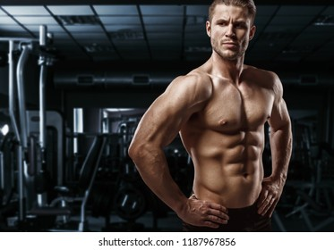 Muscular model young man exercising in gym. Portrait of sporty strong muscle. Fitness trainer. Sport workout bodybuilding motivation concept. Sexy naked torso, six pack abs. Male flexing his muscles.