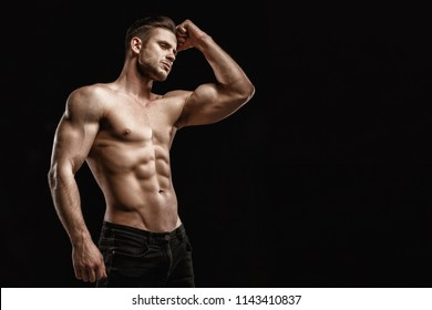 Muscular model young man on dark background. Strong brutal guy showing his biceps triceps, flexing his muscles. Sexy naked torso, six pack abs. Sport workout bodybuilding healthy lifestyle concept.