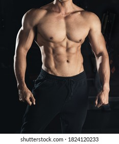 Muscular model young man on dark background. Strong brutal guy showing his biceps triceps, flexing his muscles. six pack abs. Sport workout bodybuilding healthy lifestyle concept.