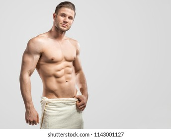 Muscular model young man in towel on grey background. Fashion portrait of strong brutal guy after shower. Sexy naked torso, six pack abs. Male flexing his muscles. Sport concept. Everyday routine.