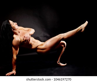 Muscular naked bodybuilder woman showing her muscles over black background.