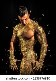 Muscular naked man covered with golden touching chin and looking down sensually on black background