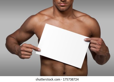 Muscular naked man holding white empty paper
