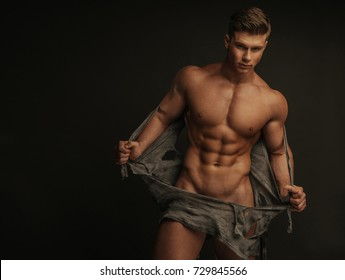 Muscular naked man tearing off his shirt