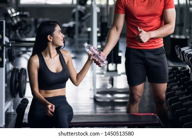 muscular personal trainer man thumb up and give bottle water to young asian attractive woman after exercise dumbbell in fitness gym. Bodybuilding and healthy happy lifesytle for elderly.