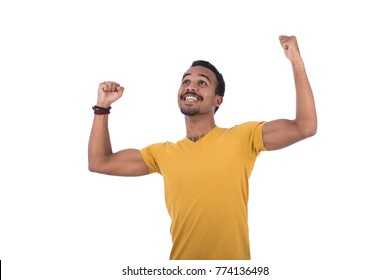 Muscular Qatari guy pumping his biceps and feeling so happy dressed a yellow t-shirt and wrist accessory. Isolated on white background.