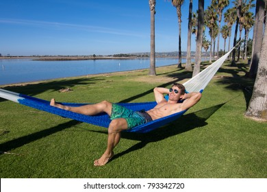 Muscular sexy Caucasian man with fit body wearing board shorts and sunglasses relaxes in Mexican hammock while tanning in park by Mission Bay in San Diego, California