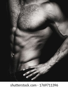 Muscular sexy man with torso. Muscular model sports young man on dark background. Sensual man with naked strong ab. Muscular torso close up. Torso concept. Black and white.