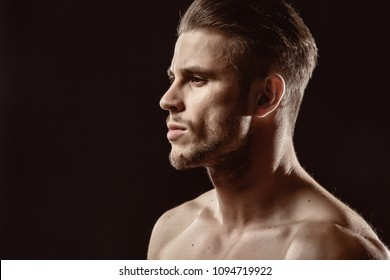 Muscular sexy model sports young man on a dark background. Portrait of sporty healthy strong brutal muscle guy with a modern trendy hairstyle.