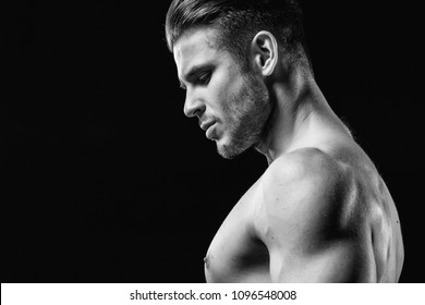 Muscular sexy model sports young man on a dark background. Black and white portrait of sporty healthy strong brutal muscle guy with a modern trendy hairstyle.