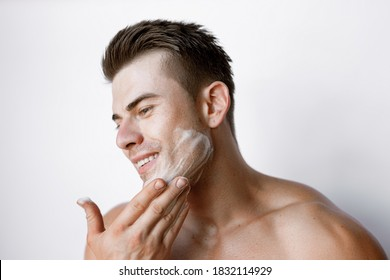 Muscular sexy model sports young man on white background. Portrait of beautiful smiling healthy guy applying foam for washing on his face. Facial skincare routine.