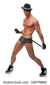 Muscular sexy naked man dancing in the studio in underwear, hat and gloves with a cane