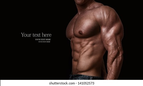 Muscular and sexy torso of young man, isolated on black background