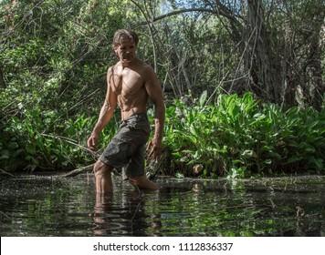 Muscular shirtless adventure man hiking through lush swamp environment