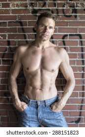 Muscular shirtless Caucasian man in blue jeans standing against brick wall with graffiti in urban setting