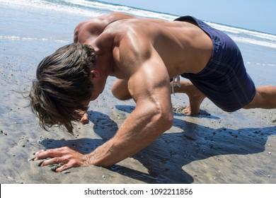 Muscular shirtless Caucasian man doing intense bear crawl workout on sandy beach on sunny day