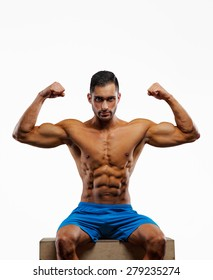 Muscular shirtless fitness man in blue shorts posing in studio on grey background