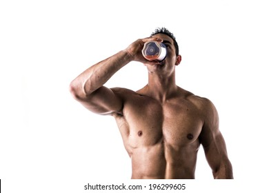 Muscular shirtless male bodybuilder drinking protein shake from blender. Isolated on white, looking up