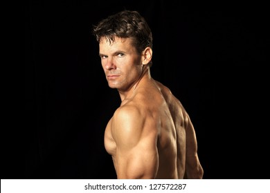 Muscular shirtless male Caucasian athlete on black background looks intensely at the camera
