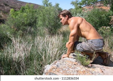 Muscular shirtless male explorer kneeling on rock ledge overlooking small valley