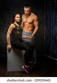 Muscular shirtless man with beard and brunette woman in sportswear posing in studio.