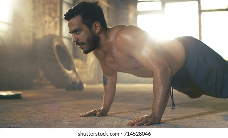 Muscular Shirtless Man Covered in Sweat Does Push-ups in a Deserted Factory Remodeled into Gym. Part of His Fitness Workout/ High-Intensity Interval Training.