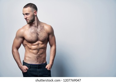 Muscular shirtless man in jeans standing at white wall posing, looking to side