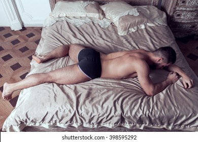 Muscular shirtless man lies on his stomach on big double bed put his head on hand